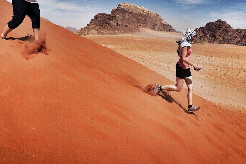 women in a desert running down a sand dune